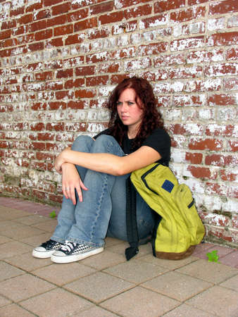 Girl with bookbag sitting against a brick wall