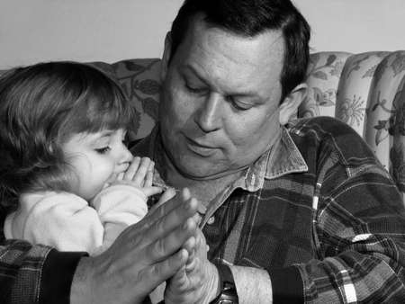 Father teaching his little girl to pray Stock Photo