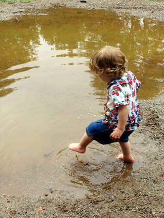 小さな女の子が mudpuddle に足を踏み入れる