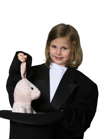 Little girl dressed in an over-sized magician costume pulling a rabbit out of a hat Stock Photo