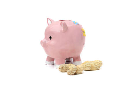Piggy bank on white with peanuts illustrating concept of dwindling value of savings Stock Photo