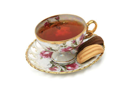 Antique china tea cup with hot tea and cookies isolated on white Stock Photo