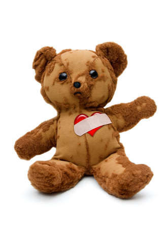 Tattered and tearful vintageTeddy bear with bandaged broken heart on white
