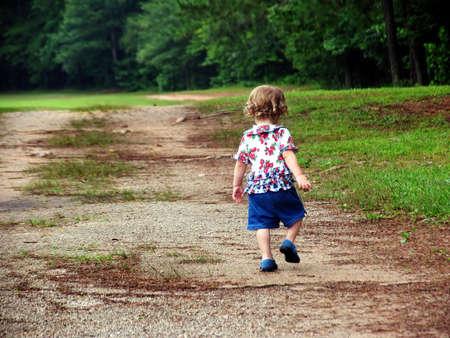 Little girl walking up a dirt road