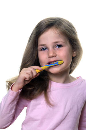 Cute little girl using a toothbrush to brush her baby teeth Stock Photo