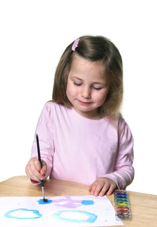 Cute little girl with watercolor paints and paintbrush enjoying painting on paper photo