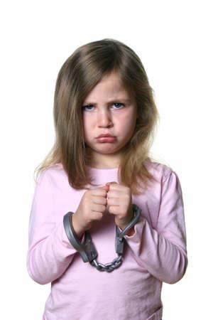 handcuffed: Klein meisje met boze uitdrukking geïsoleerd op witte achtergrond dragen speelgoed handboeien