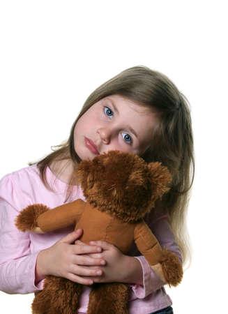 looking into camera: Bambina in possesso di un orsacchiotto isolato su bianco e guardando la telecamera con l'espressione pensierosa
