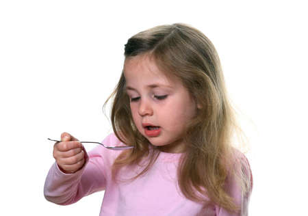 Little girl holding a spoon about to take liquid medication photo