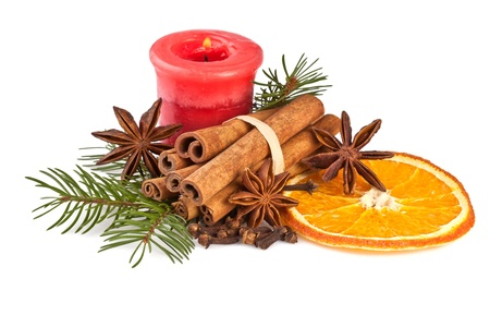 christmas decoration with fir branch, candle, cinnamon on white