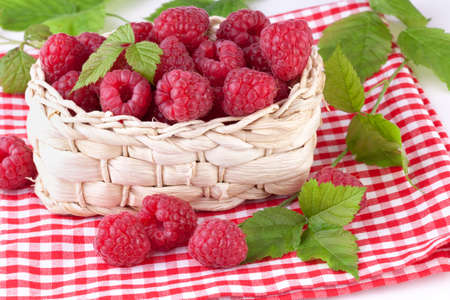 raspberries with leaves in basket photo