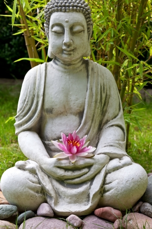 Buddha sculpture with lotus and bamboo leaves in background photo