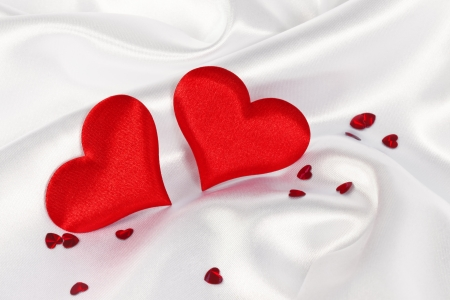 love story: two red heart on white silk