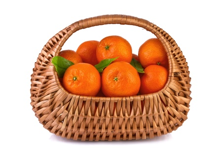 tangerines with leaves in beautiful basket isolated on white photo