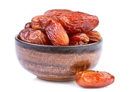 frutas secas: d�tiles secos de color marr�n taza aislado en blanco