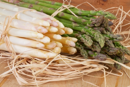 bundle of green and white asparagus on wooden table