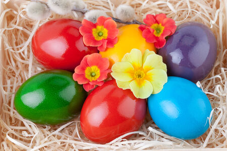 Easter Eggs over Straw decorated with Flowers photo