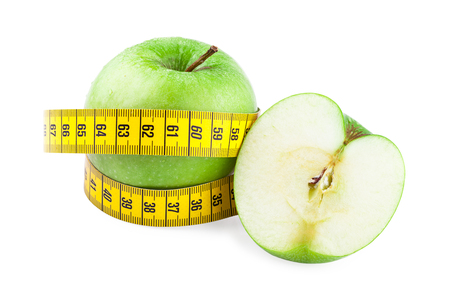 Healthy food and diet concept. Green apples and measuring tape isolated on  white background photo