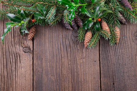 Christmas Tree Branch with Fir Cones over Old Wooden Background photo