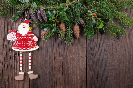 Santa Claus with Fir Branch over Wooden Background photo