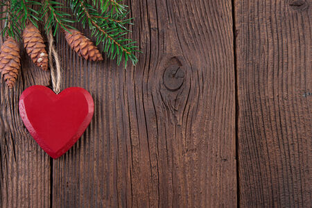 Red Heart with Fir Branch over Wooden Background