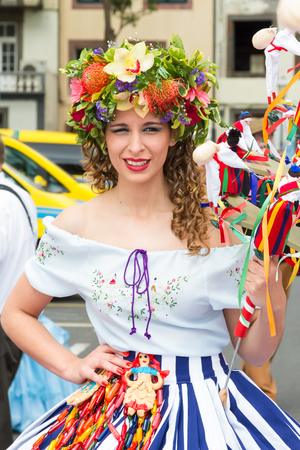 participate: FUNCHAL, MADEIRA - APRIL 20, 2015: A beautiful woman smiles as she she prepares to participate in the Madeira Flower Festival.