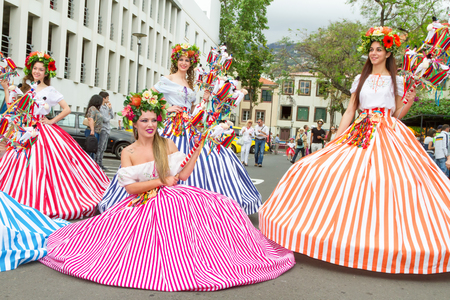 flower parade: FUNCHAL, MADEIRA - APRIL 20, 2015: Performers with colorful and elaborate costumes taking part in the Parade of Flower Festival on the Madeira Island, Portugal. Editorial
