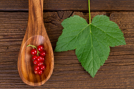 redcurrant: redcurrant in wooden spoon and leaf on wooden background Stock Photo