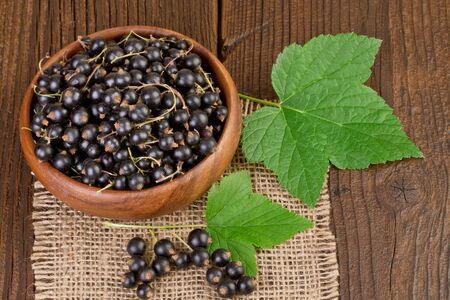 blackcurrant: blackcurrant berries on rustic wooden background Stock Photo