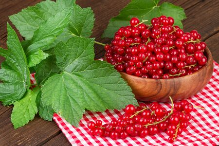 redcurrant: redcurrant berry in wooden bowl