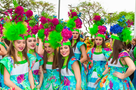 participant: FUNCHAL, MADEIRA, PORTUGAL - APRIL 19, 2015: Performers with colourful  costumes taking part in the Parade of Flower Festival on the Madeira Island, Portugal.