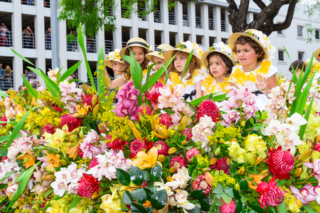 flower parade: FUNCHAL, MADEIRA, PORTUGAL - APRIL 19, 2015: Children in festive Floral Floats at the Madeira Flower Festival Parade, Funchal, Madeira, Portugal Editorial