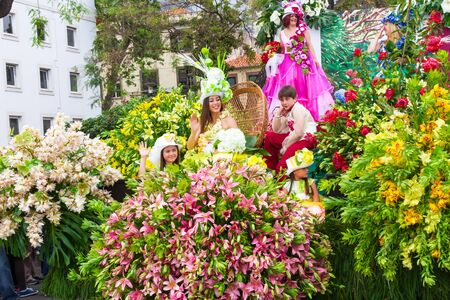 floats: FUNCHAL, MADEIRA, PORTUGAL - APRIL 19, 2015: Participants in Floral Floats at the Madeira Flower Festival Parade, Funchal, Madeira, Portugal Editorial