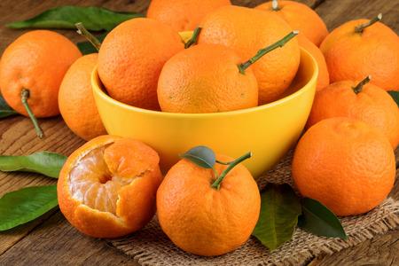 citrus reticulata: Mandarins Tangerines in Yellow Bowl Stock Photo