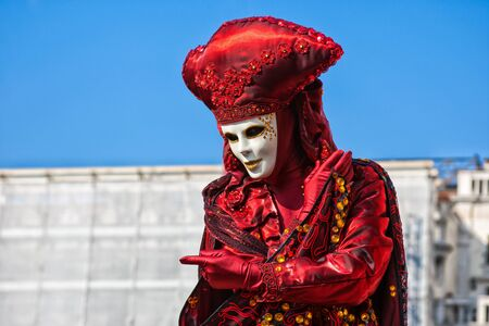 saint mark's square: Carnival Mask dressed in red Carnival costume poses in Saint Marks Square Venice, Italy