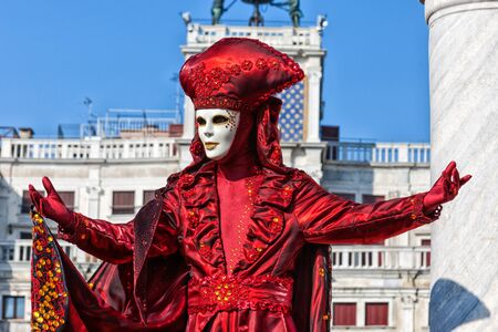 Carnival Mask dressed in red Carnival costume poses in Saint Marks Square Venice, Italy