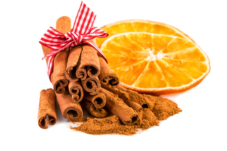 dried orange: Dried orange slices with cinnamon sticks and cinnamon powder on white.