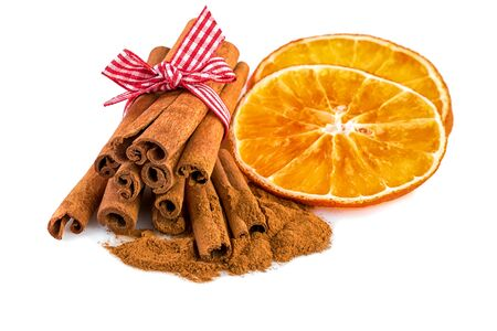 christmas spices: Christmas spices with orange slices and cinnamon sticks on white.