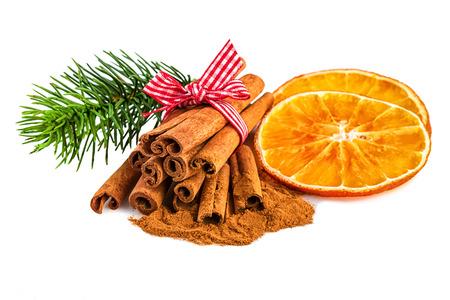 Plátky pomeranče se skořicí a jedle větve na bílé. Vánoční rustikální dekorace na bílém pozadí.