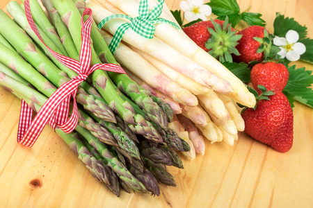 white asparagus: Green white asparagus with fresh strawberries on bright wood. Healthy cooking concept.