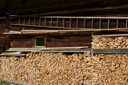 alpine hut: Firewood stacked by the alpine hut. Rustic farming scene.