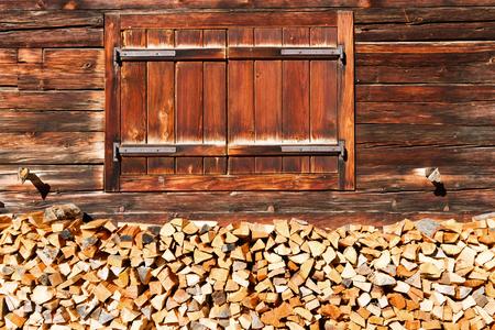 Gesloten venster en gestapeld brandhout van oude alpiene hut. Landelijk alpine landschap.