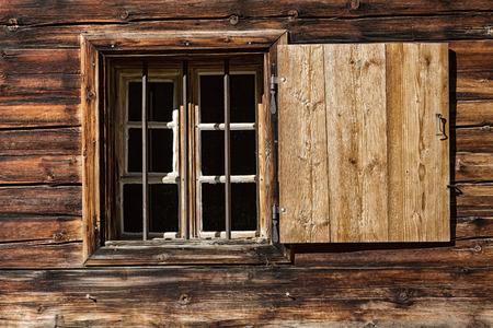 alpine hut: Window of a wooden alpine hut. Rustic background.