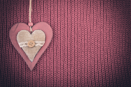 pale color: Wood heart on wool knitted fabric. Christmas rustic vintage background pale color vignette.