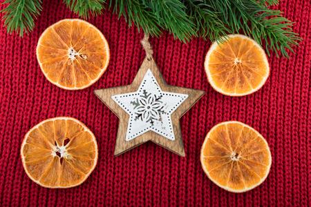 estrella de la vida: Christmas decoration with wooden star on red wool fabric. Christmas rustic still life. Foto de archivo