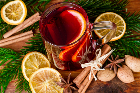 Christmas mulled wine with spices on wooden background. Top view.