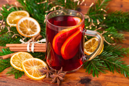 Mulled wine festive decorated on old wooden background