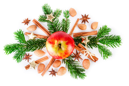 Christmas composition with red apple and aromatic spices on white. Top view, sight from above.