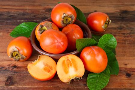 Persimmons kaki fruits on old wooden Stock Photo