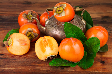 Ripe Persimmon fruits with vintage tea pot. Oriental East Persian still life.